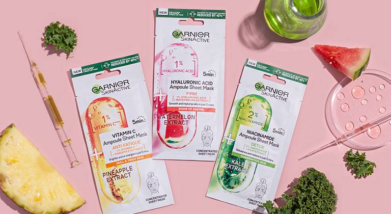 ampoule sheet masks with decorative ingredient assets laid on pink background